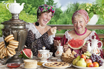 Two cheerful women drinking tea outdoors