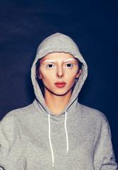 Hipster girl in grey hoodie gainst dark background