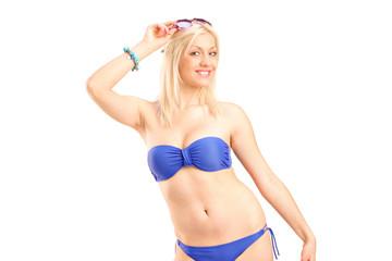 Blond smiling woman in blue bikini posing