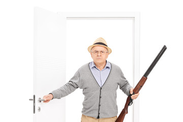Angry senior man with hat holding a shotgun and walking through