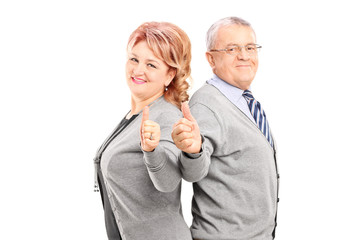 Confident and happy mature couple giving thumbs up and looking a