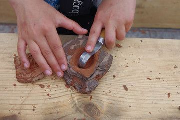 Carving a wooden bowl using hand tools.