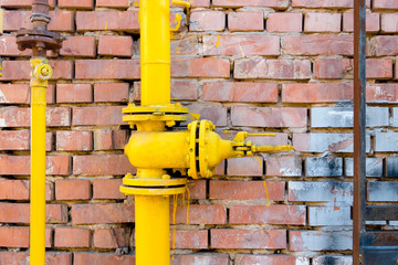 Yellow gas pipe and valve on red brick wall, copyspace