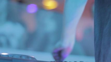 DJ playing records at night club, people enjoying music, party
