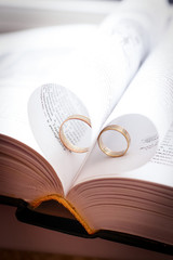 Couple of golden wedding rings in heart shaped papers in book