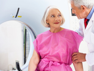 Mature doctor reassuring female patient about undergoing scan