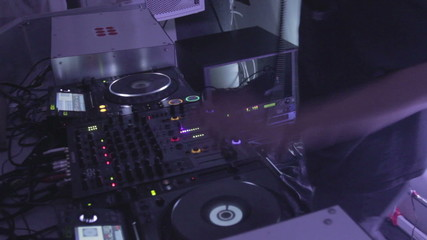 DJ scratching platter at turntable, creating atmosphere at club