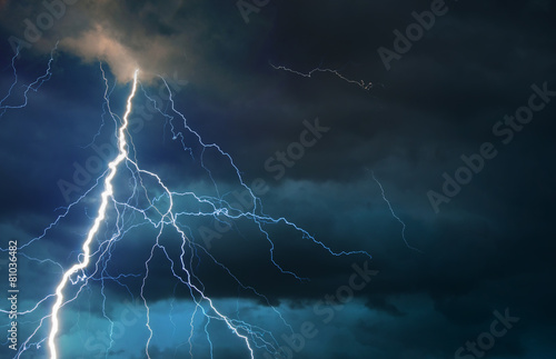 Leinwanddruck Bild Fork lightning striking down during summer storm