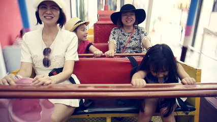 Happy Asian child with mother playing speed boat