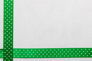 Dotted green blue ribbon frame on white cloth