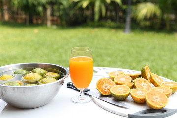 Glass of freshly pressed orange juice with sliced orange half on