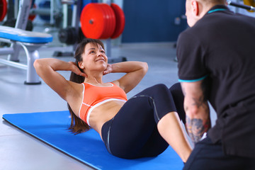 Woman does situps with coach in training gym