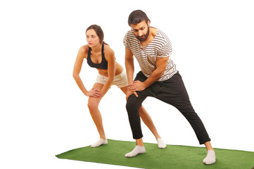 Athletic couple warming up on exercise mat