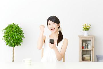 スマートフォンを持ってガッツポーズする女性