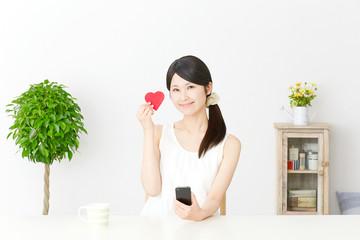 スマートフォンとハートを持つ女性
