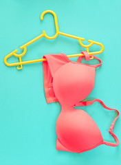 Summer concept, bra on coat hanger on blue. (Pop art style)