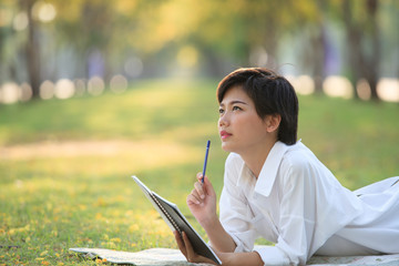 young woman lying on green grass park with pencil and note book