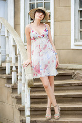 girl in the hat and summer sundress on the stairs