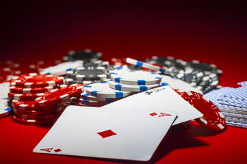 a pile of poker chips and a pair of aces