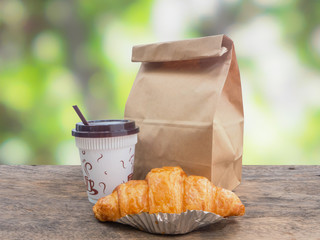 coffee and croissant with paper bag on table