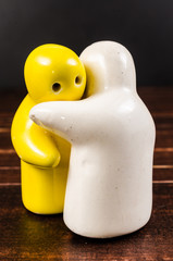 concept abstract of hugging ceramic dolls on wooden table