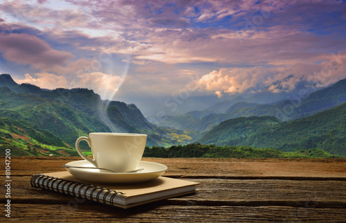 Fotobehang Thee Morning cup of coffee with mountain background at sunrise