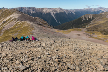 tourists resting on mountain range in Nelson Lakes National Park