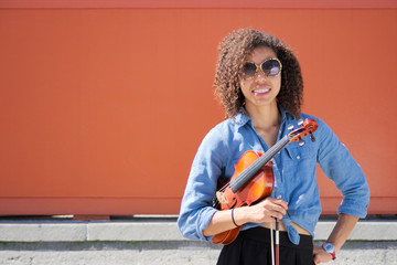 Female violinist with violin under arm smiling at camera
