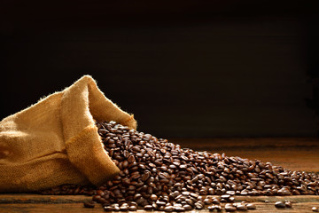 Coffee beans in burlap sack on wooden table