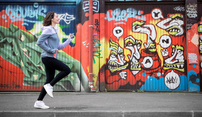 Young attractive woman running downtown