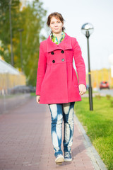 Beautiful woman in red coat walking autumn street.