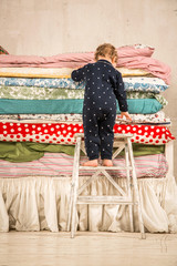 Child climbs on the bed - Princess and the Pea.