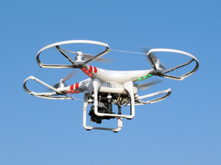 Drone quadcopter with digital camera in flight.