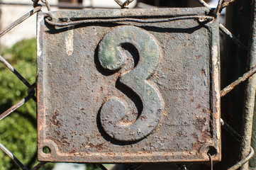 Old retro cast iron plate with number 3 on it