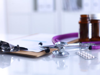 Doctor's stethoscope  with folder and bottle of pills on the
