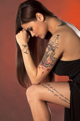 pretty young woman with tattoos posing in a black dress
