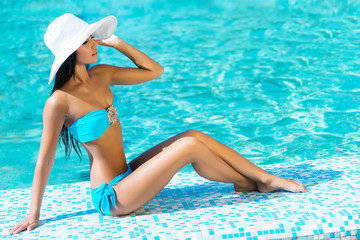 Beautiful and sporty girl relaxing in a pool at summer