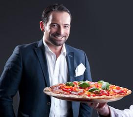 Geschäftsmann im Anzug mit Pizza Salami lächelt glücklich