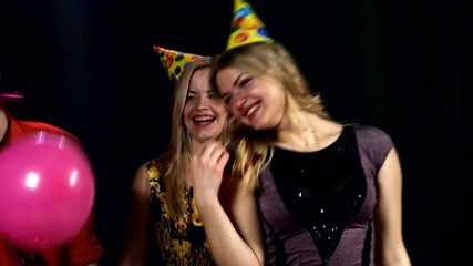 Two blondes in the foreground dancing  a nightclub: birthday