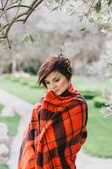 Pretty young woman standing in a park wrapped in a blanket
