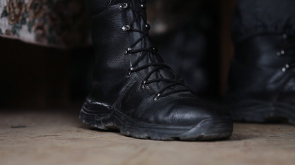 soldier ties the laces on ankle boots