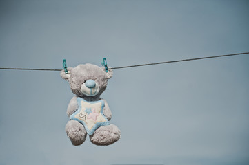 The toy bear hangs on clothespins 2358.