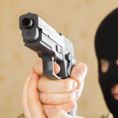 Man in black mask holding gun and ready to use it - studio shot
