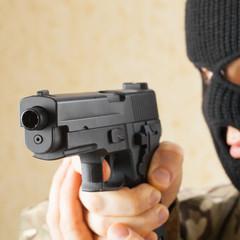 Man in black mask holding gun before him - studio shot