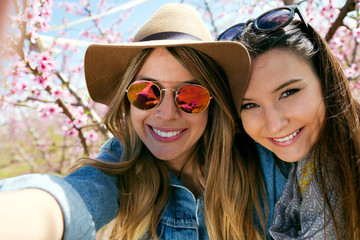 Two beautiful young women taking a selfie in the field.