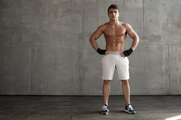 Man with athletic body  background to the concrete wall