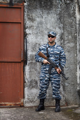 Caucasian military man with black sunglasses in urban warfare ho