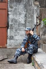 Caucasian man in urban warfare sitting with rifle protecting gat