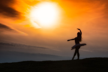 Ballerina silhouette, dancing alone in nature in the mountains a