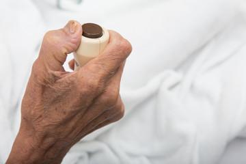 Hand pressing emergency nurse call button